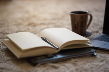 An arrangement of an open black journal and pen with a laptop and coffee mug on a rug on the floor, with warm light coming from above