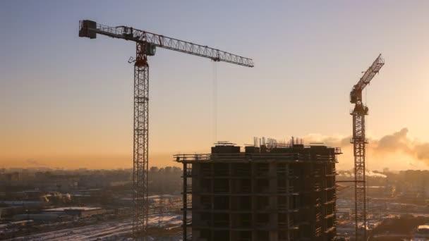 Zimní výstavba výškové činžovního domu v rozlišení 4k na pozadí zapadajícího slunce - aktivní práce stavební jeřáby a pracovníků
