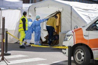 Covid-19 'u uyarın. İlk AID için triyaj hastanesi çadırı, Corona Virüsü bulaşmış hastalar için mobil bir tıbbi birim. Koruyucu maskeli doktorlar girişteki hastaları kontrol edin..