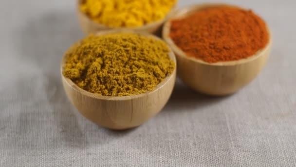 Sada různých druhů koření v dřevěných miskách - paprika, kurkuma, kari. Otočné video.
