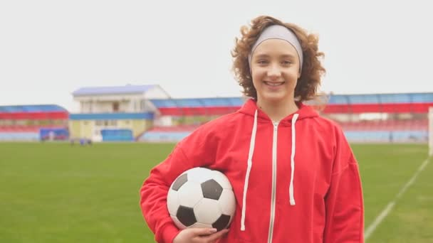 Portrait of smiling female football player with soccer ball at stadium
