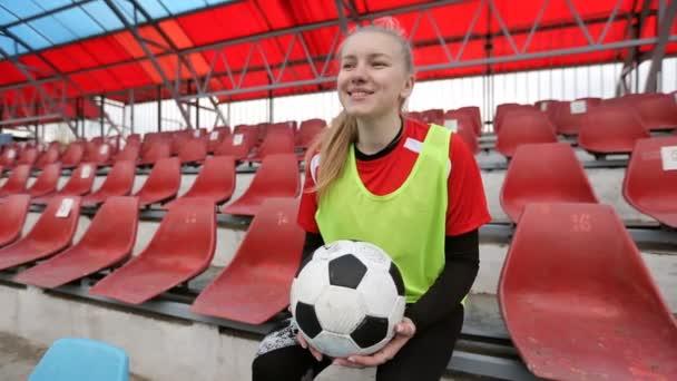 Mladý usmívající se dívka fotbalista s fotbalovým míčem sedí na sedadlech na fotbalovém stadionu a snění