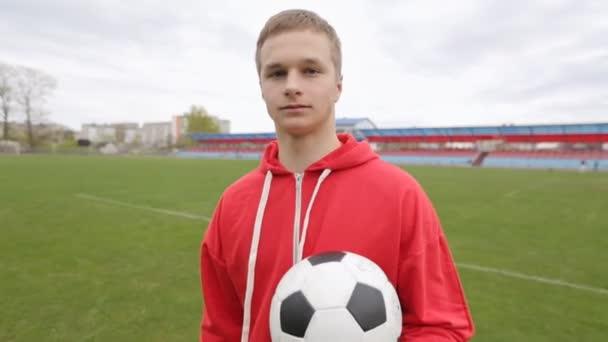 Portrét sebevědomého mladého fotbalisty s fotbalovým míčem na stadionu