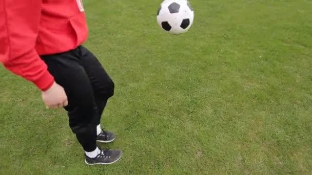 Fotbalista žongluje s fotbalovým míčem nohama, zpomaluje
