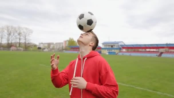 Junger Fußballer jongliert mit dem Kopf