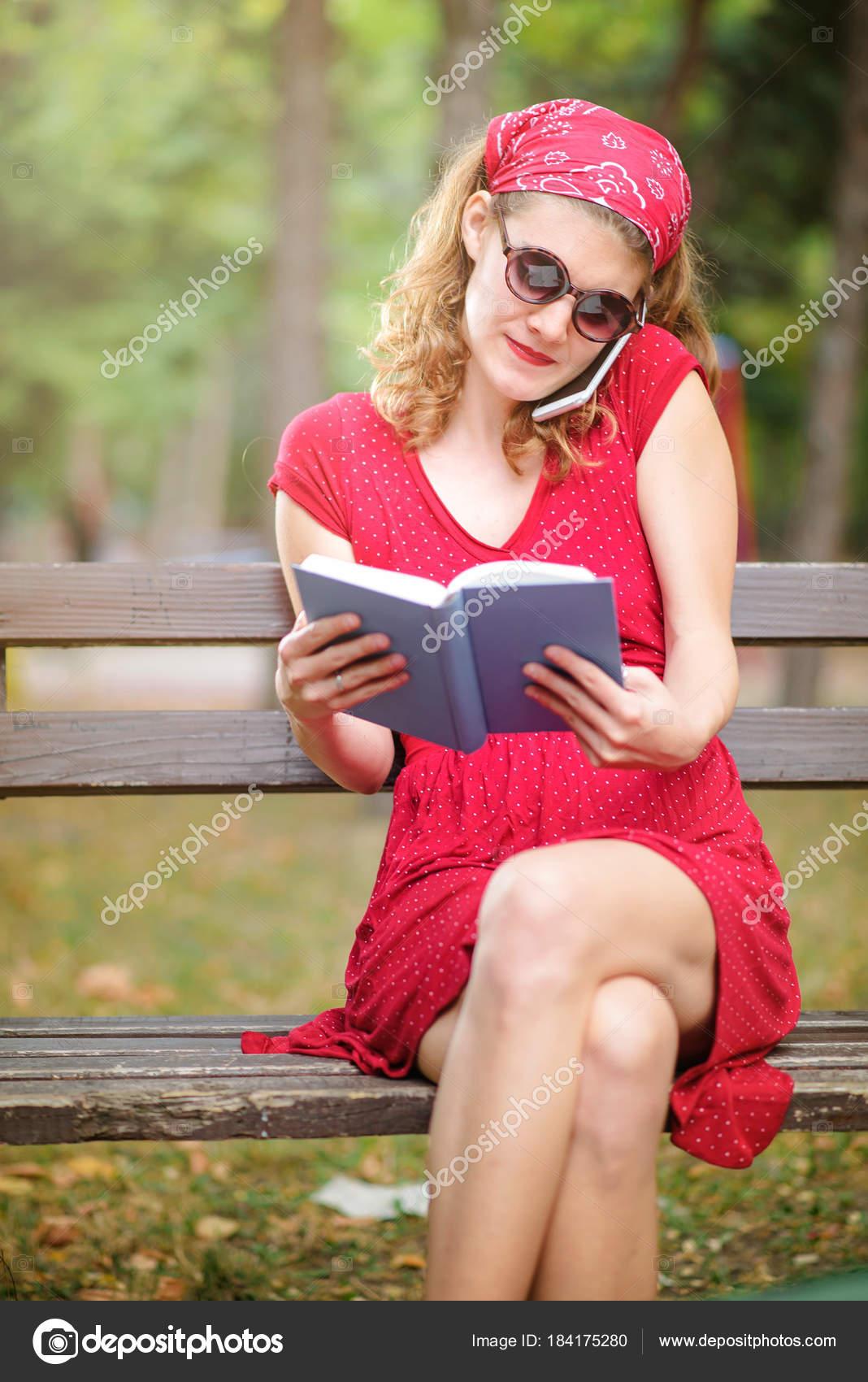 881541da5 Mujer joven en un vestido vintage rojo leyendo un libro y tener una charla  rápida con un amigo sobre su teléfono