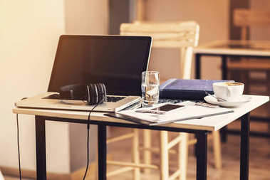 Headphones on a laptop keyboard, music arranger setting, warm yellow tone