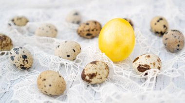 Yellow handmade Easter egg with brown quail eggs on beautiful tablecloth. Easter background.