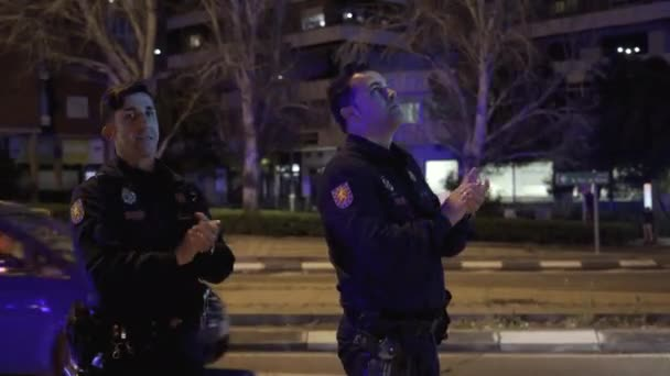 Two National Police officers applaud medical workers from the Fundacion Jimenez Diaz hospital who are fighting coronavirus