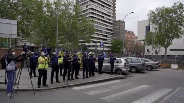 Several Madrid Municipal Police officers and paramedics applaud and cheer up medical workers from Fundacion Jimenez Diaz hospital who are fighting coronavirus