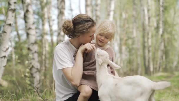 Eine junge Mutter und zwei kleine Töchter spielen mit einer Ziege im Wald