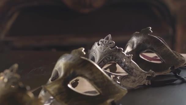Gold- und silberne venezianische Masken mit Riemen liegen auf einem schäbigen Tisch in einem Lichtstrahl und werfen einen Schatten. Reibungslose Bewegung an einem Sommertag