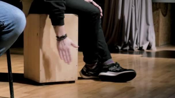 Blízký záběr muže, který poklepává na rytmus, zatímco mlátí rukou do dřevěné krabice při zkoušce hudební kapely. Akcie. Hudba a umění koncept, muž sedí na krabici a bití rythm.