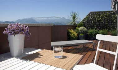 Terraza soleada con mesa, silla, vaso de agua y plantas y vistas a una montaa