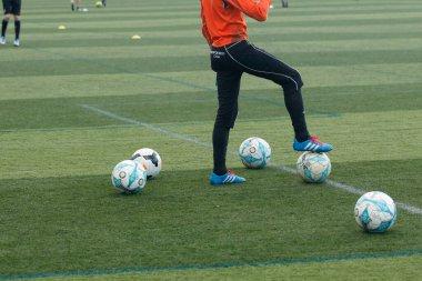 Jugador de Futbol con balones on campo de entrenamiento
