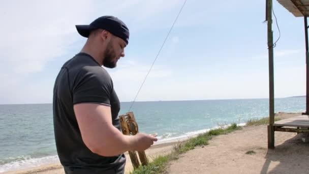 Der Typ trainiert in der Nähe des Meeres, am Strand, mit Blick auf Meer und Sand, boxt, rennt, telefoniert, wirft einen Meeresstein