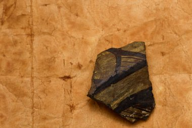 Archaeological find: a fragment of ancient pottery on a background of old paper