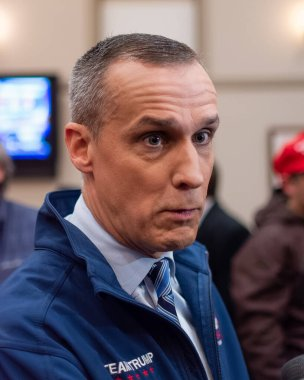 Corey Lewandowski surrounded by press chooses his words carefully when responding to reporters questions during the GOP 2020 primary celebration in Bedford New Hampshire. He is wearing a blue fleas jacket blue shirt and blue tie. Microphones, cameras