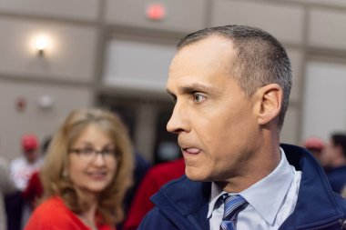Corey Lewandowski in the middle of a press scrum moistens his lips between responses to questions during the GOP 2020 primary celebration in Bedford New Hampshire. He is wearing a blue fleas jacket blue shirt and blue tie. A woman in red is focused o