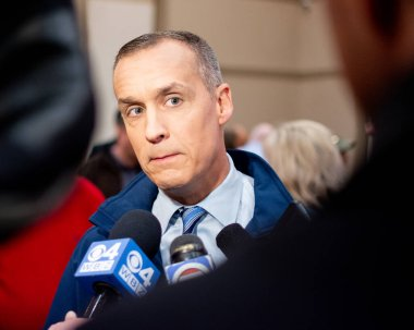 Corey Lewandowski surrounded by press scrum grimacing while listing to reporters questions during the GOP 2020 primary celebration in Bedford New Hampshire. He is wearing a blue fleas jacket blue shirt and blue tie. A woman in red is focused on watch