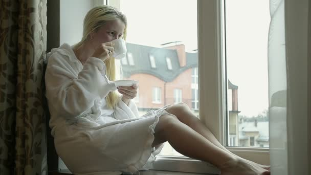 Girl in Bathrobe Drinking Coffee at Home Near the Window and Looking Out