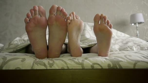 Detailní záběr mladý pár dotýkat navzájem nohy pod dekou