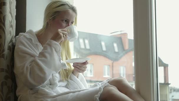 Girl in Bathrobe Drinking Coffee at Home Near the Window