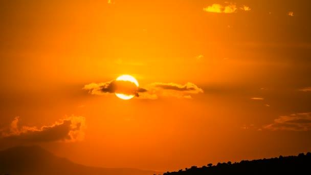 Sonnenuntergang durch die Wolken über dem Berg im Zeitraffer