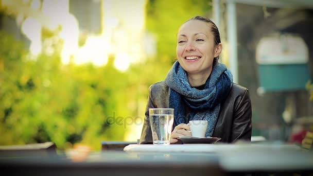 Beautiful Young Woman Drinking Coffee in an Outdoor Cafe