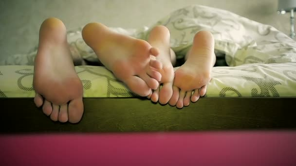 Close-Up Couple Touching Each Others Feet Under the Blanket