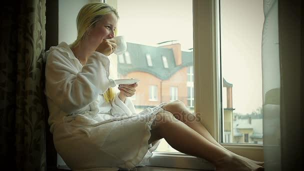 Happy Girl in Bathrobe Drinking Coffee at Home Near the Window