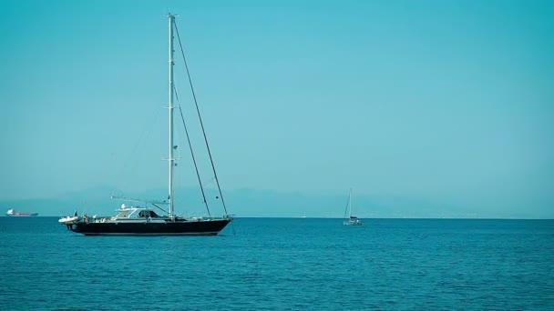 Velká jachta kotví v zátoce pohled z pobřeží
