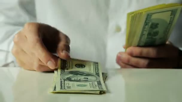 Close-Up of a Busnessman Fast Lays Out Hundred Dollar Bills on the Table
