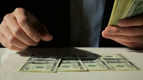 Man in the Suit Lays Out Hundred Dollar Bills on the Table