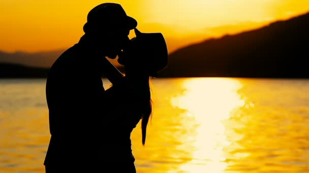 Silhouette couple in love kisses passionately in a trip by the sea on the sunset.Happy vacation