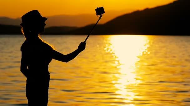 Silueta dívka střílí selfie na mobilním telefonu na odpočinek u moře na západ slunce