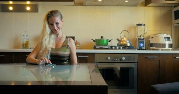 Dolly egy aranyos lány ül egy asztalnál, a konyhában egy napsütéses napon, és beír egy üzenetet a smart-phone.