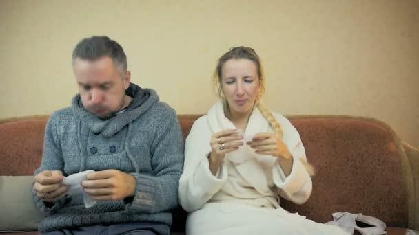 Zeitlupe: Mann und Mädchen niesen und wischen Rotz mit Taschentuch ab, wenn sie zu Hause auf dem Sofa sitzen.