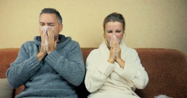 Junge Kerle und Mädchen niesen und wischen Rotz mit einem Taschentuch, das zu Hause auf dem Sofa sitzt.