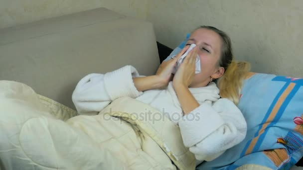 Zeitlupe: Junges Mädchen im Bademantel hustet und niest auf dem Sofa.