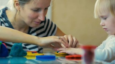 SLOW MOTION: close-up a mom teaches her three-year-old daughter to sculpt figurines from plasticine at home.