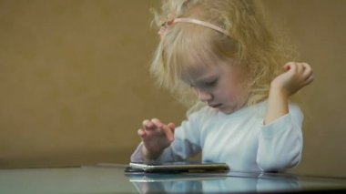 SLOW MOTION: close-up a little girl of three-year-old choose a cartoon on the Internet on smartphone at home.