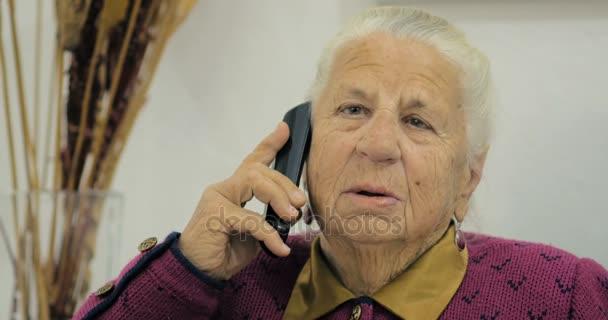 Detail stará babička osmdesát tři let mluvit její přítel na telefonu při sezení na židli v pokoji.