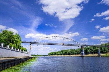 People walking on metal footbridge across river Sozh in Gomel, Belarus