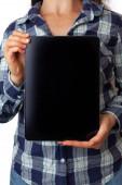 Junge Frau im karierten Hemd hält leeres schwarzes Tablet mit Kopierplatz in der Hand