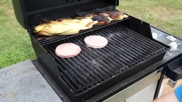 Umístění hovězích hamburgerů na gril
