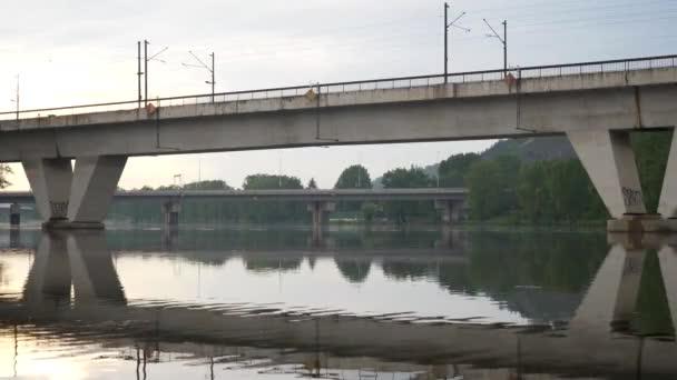 vlak projíždí přes řeku Vltavu v Praze v České republice. Na povrchu je vidět odraz mostu.