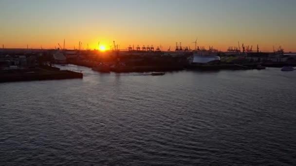 Blick auf den Hamburger Hafen in der Hafenstadt an der Elbe bei Sonnenuntergang / Dämmerung