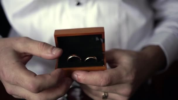 A man in a black suit holds wedding rings in a wooden box