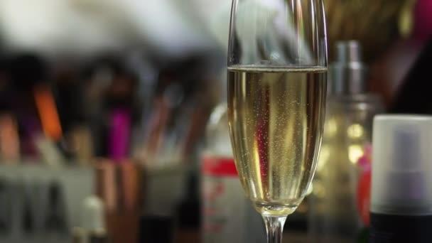Ein Glas Champagner steht auf dem Tisch und darin laufen Gasblasen..